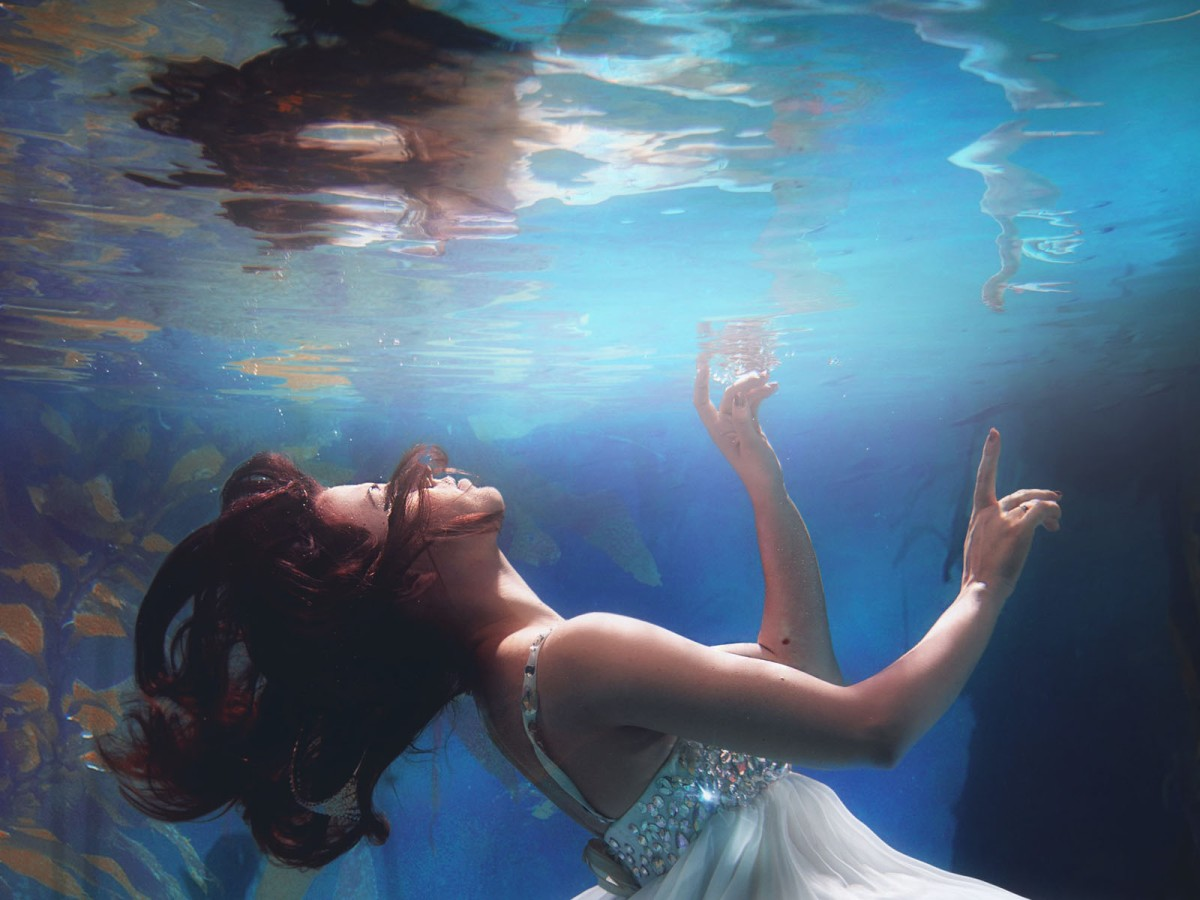 woman underwater gazing up at the surface